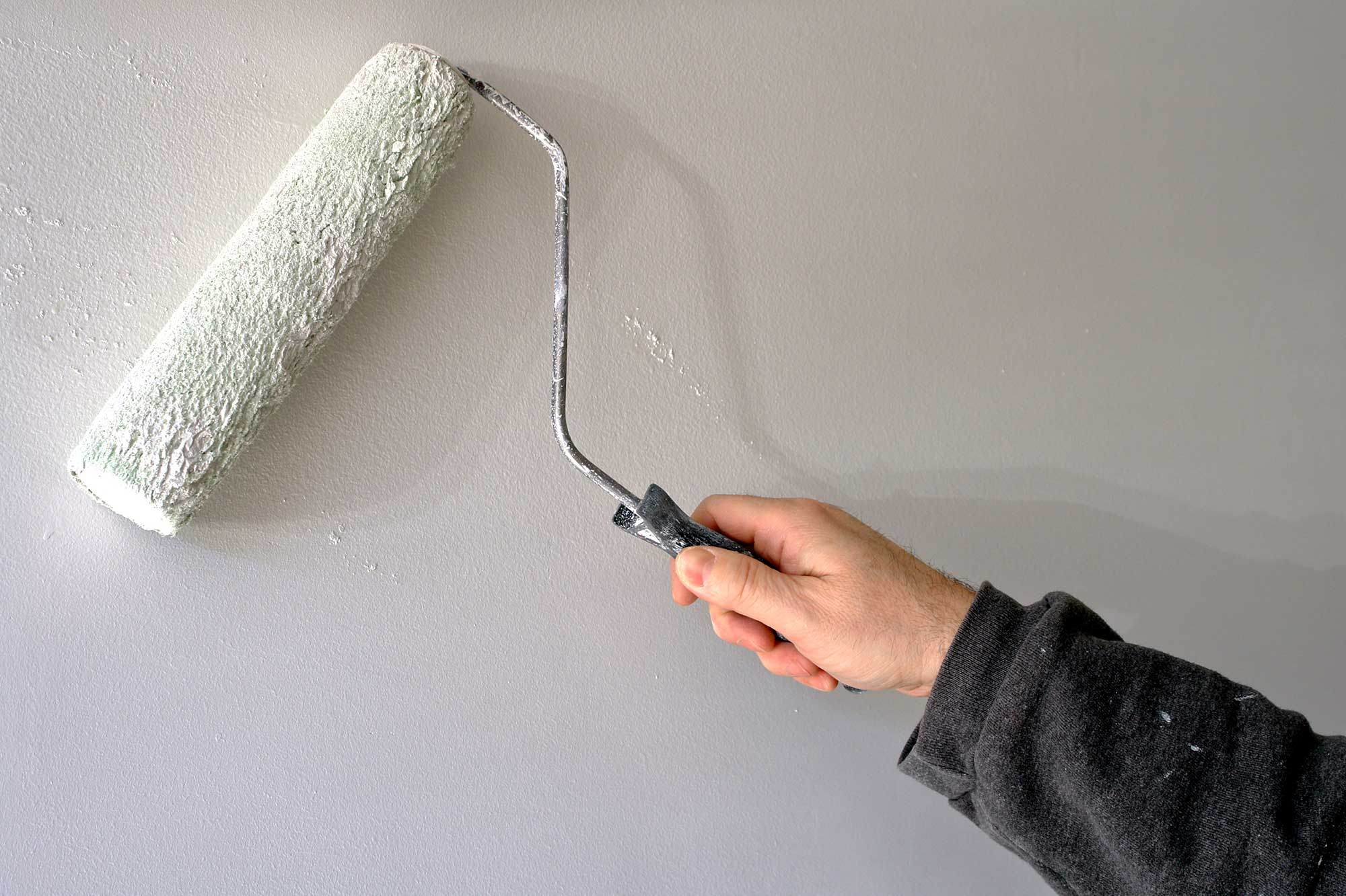 Man painting a wall with a roller