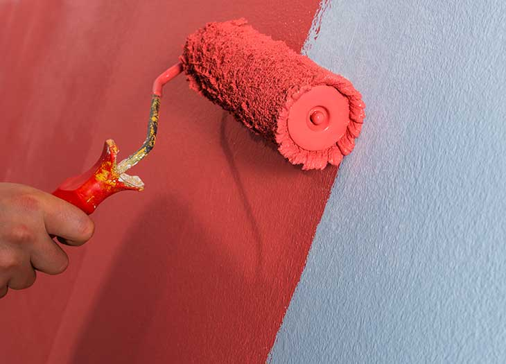 Wall being painted red with a roller