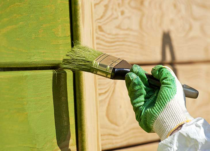 Wood being painted green with a paint brush